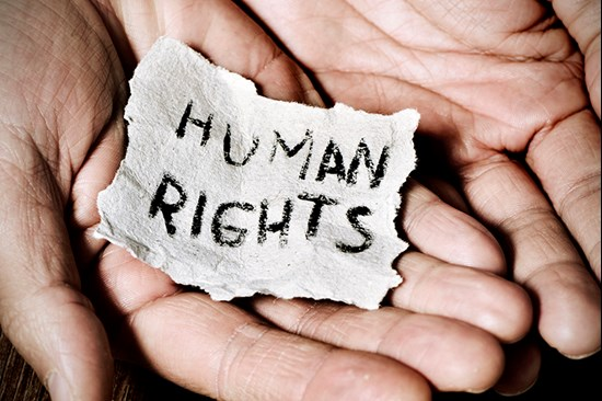 Hands holding piece of paper with human rights written on it
