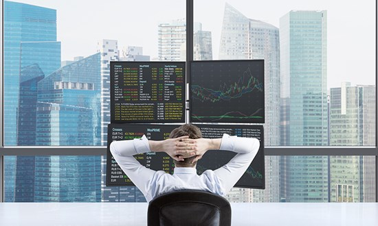 Corporate worker facing stocks on computer screen