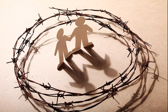 Paper people surrounded by barbed wire