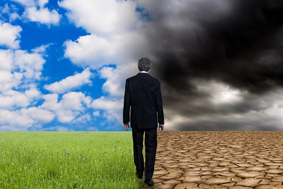 Man in suit looking out at green meadow versus dry cloudy landscape