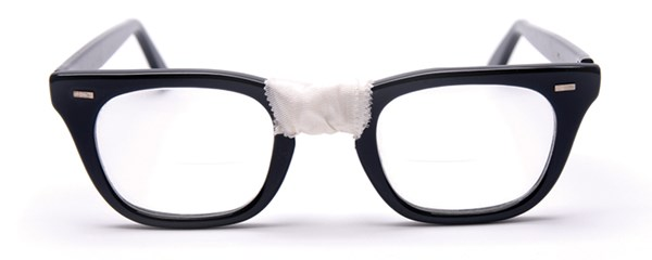 Pair of eyeglasses taped in the middle