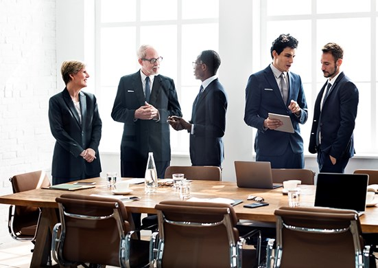 People talking around board room table
