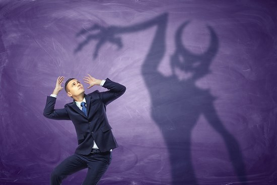 Business man with devil-shaped shadow