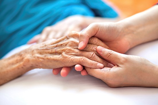 Young female hand holding elderly female hand