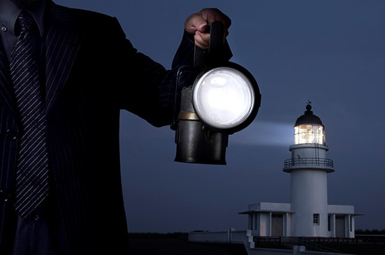 Business person holding lantern with lighthouse in the background
