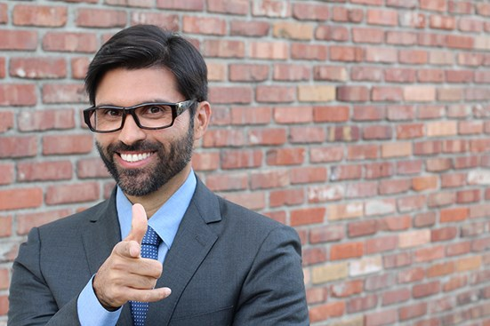 Businessman smiling at camera with his finger pointed at viewer
