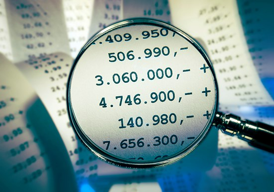 Magnifying glass showing accounting figures