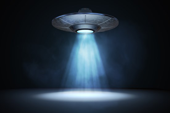 Spaceship hovering above ground with spotlight