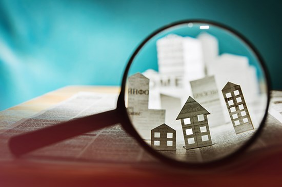Magnifying glass focussed on paper houses