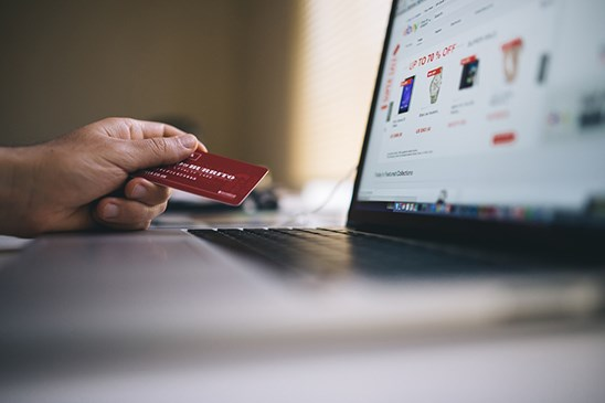 Person holding credit card near laptop