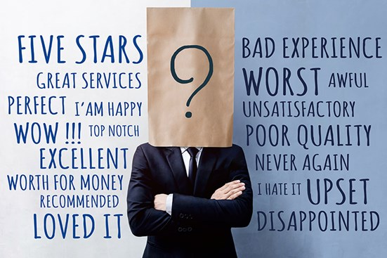 Businessman with brown paper back over head, standing against wall with reputation themed words