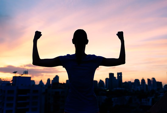 Silhouette of person holding strong arms pose against sunset