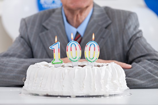 Businessman sitting in front of cake with 100 candle on top