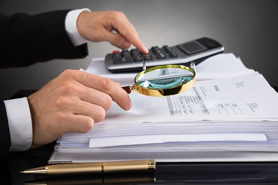 Businessman looking over documents with magnifying glass