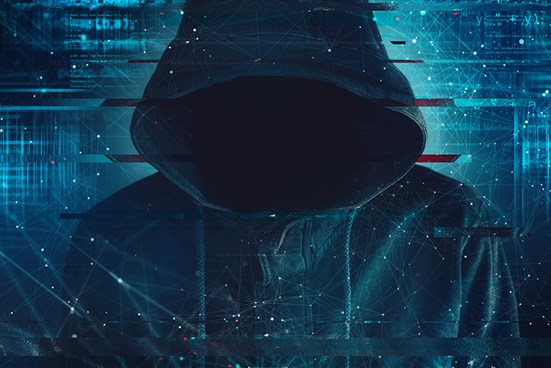 Hooded figure against data/technology background